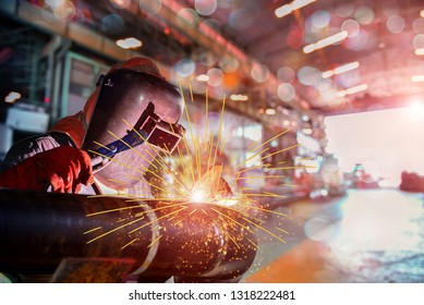 Welder industrial in factory welding with bokeh, light spark wear equipment protective PPE for safety