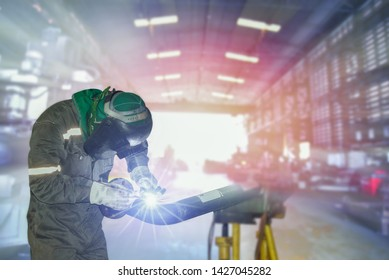 Welder industrial in factory welding process TIG with gas argon, light spark from working light grinding , equipment protective PPE for safety