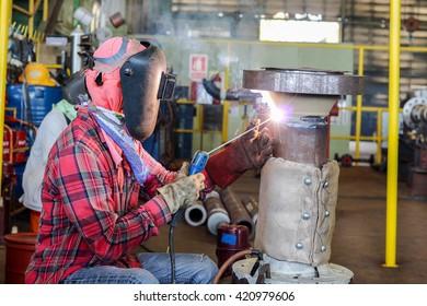 Welder man welding in workshop
