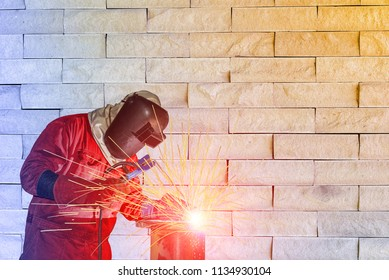 welder man working welding process success at project site with steel pipe on sparks with sparks light wear protective equipment and mask on wall stone background concept