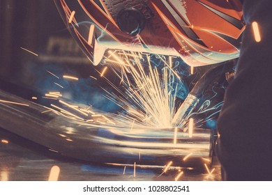 Welder in mask welding metal and sparks metal. Toned image. Welding with sparks from the side view close