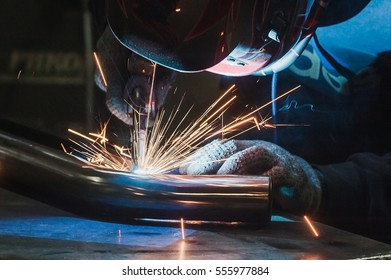 Welder in mask welding metal and sparks metal close
