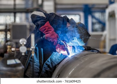 The welder in the mask welds the metal part