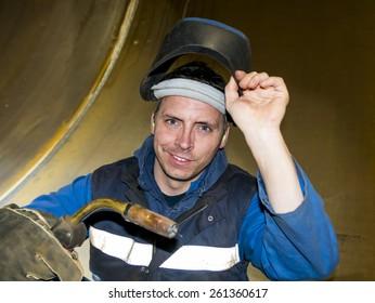 welder with mig/ mag welding gun in his hand, lifting his welding mask with his other hand