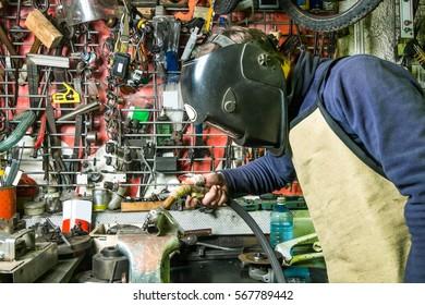 a welder n the welding mask working in the garage