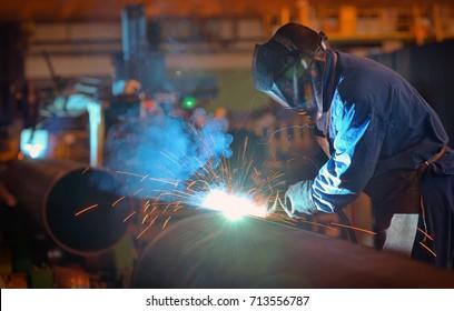 Welder performs welding large diameter pipe inside plant