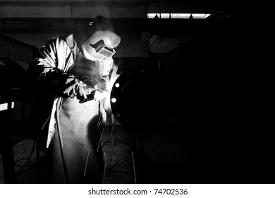 Welder with protective equipment weld metal pipes in factory