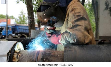 Welder with protective equipment welding outdoors.  Welding. Metal works.