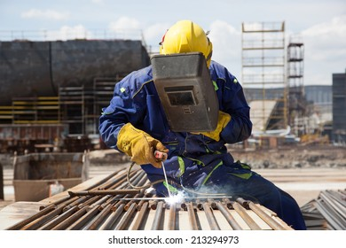 welder with protective equipment welding steel bars outdoors