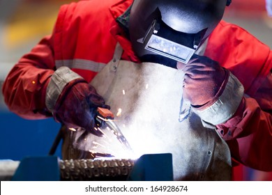 Welder with protective mask welding metal and sparks