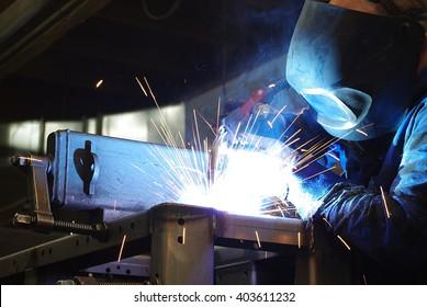 Welder with protective mask welding metal.