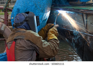 Welder in a protective mask when working. Photo taken on: August 25th, 2011