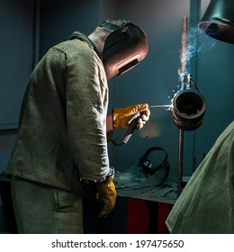 Welder with protective mask working in a steel factory