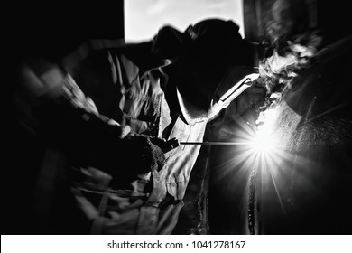 welder is repairing the defective area of the weld inside the parts of chemical apparatus