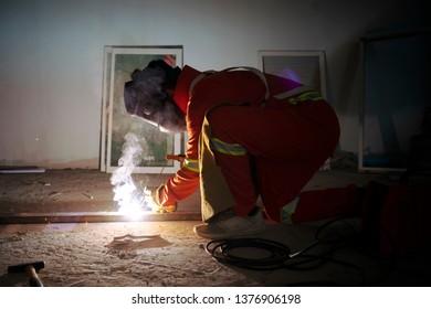 welder with safty dress is welding metal part