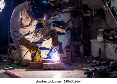 Welder sit working with protective mask and uniform in the factory