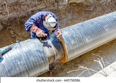 Welder is in trench working hard, arc welding pipeline.