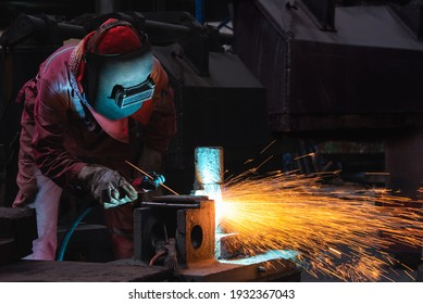 Welder use carbon air arc gouging for hot work cutting or gouging heavy metal steel structure in the fabrication factory.