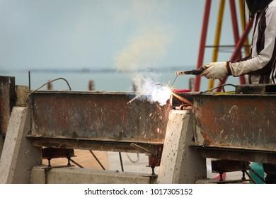 Welder is welding beam to construction the bridge.