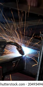 A welder welding the framework for industrial tanks