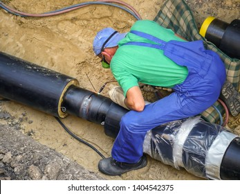 Welder welding heating installation pipes in the trench