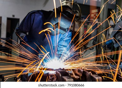 welder is welding metal part in car factory