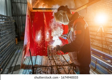 A welder is welding metal parts. Rebar assembly plant for reinforced concrete piles.
