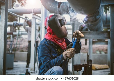 Welder is welding pipe at construction site