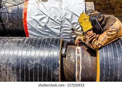 Welder is welding a pipe in a trench.