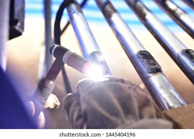 The welder is welding the plate to the pipe with Tungsten Inert Gas Welding process (TIG). The welder wears protective equipment with a mask and heat resistant gloves
