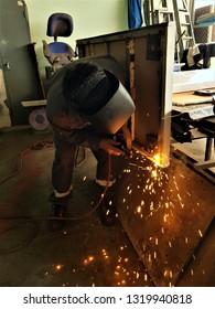 The welder is welding the steel in the factory.