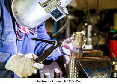 Welder is welding Tungsten Inert Gas welding, TIG weld for making new stainless flexible hose in manufacturer workshop / TIG welding torch