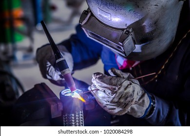 Welder is welding Tungsten Inert Gas welding, TIG weld for making new stainless flexible hose in manufacturer workshop / TIG welding torch
