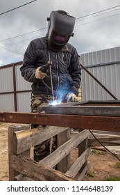 Welder welds metal at the construction site