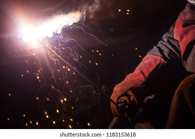 The welder welds the metal structures with the help of an electrode. In the hand, a welder holds an electrode. Close-up