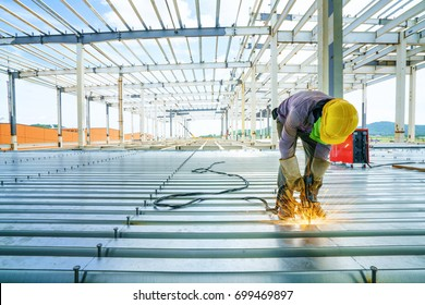 Welder are welds re-bar shear keys metal deck slab of mezzanine floor in construction industrial building