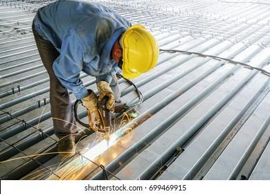 Welder are welds re-bar shear keys metal deck slab of mezzanine floor in construction industrial building