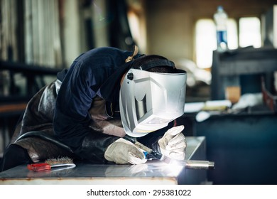 Welder at work using welding mask, tools and machinery on metal. Selective focus.