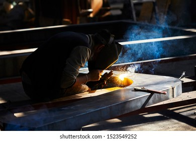 welder working with electrode at semi-automatic arc welding in manufacture production