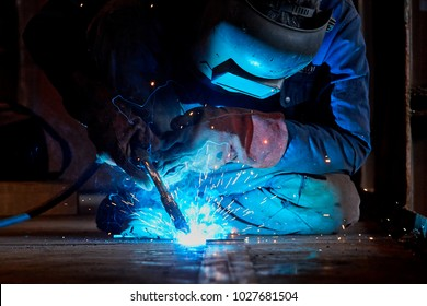 Welder working at the factory  in a welding mask and welders leathers