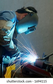 Welder working on metal tubes