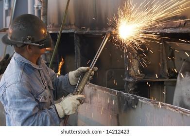 a welder working a torch at shipyard