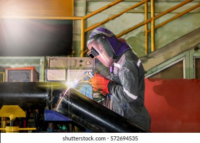 Welder working a welding metal pipe with protective mask and sparks in factory
