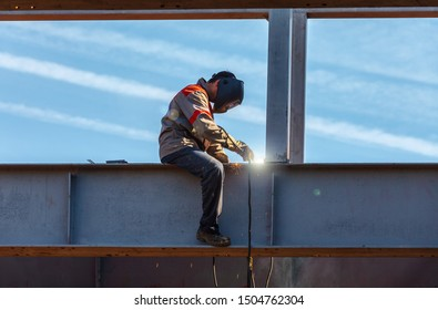 A welder works at a height against the sky and welds an iron structure