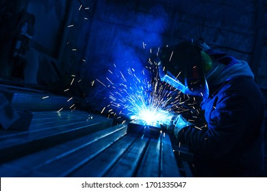 The welder works with a metal profile. Assembly of metal structures in industrial production