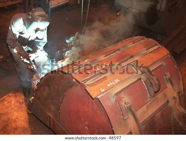 a welder works on an excavator bucket
