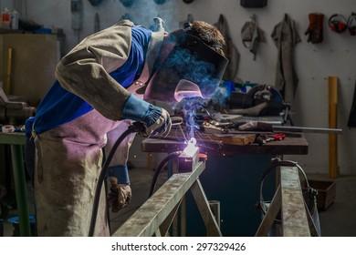 Welder in workshop manufacturing metal construction
