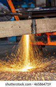 Welder in workshop manufacturing metal construction by cutting to shape using huge orange sparks