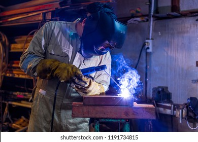 Welder workshop training a welding metal with protective mask and uniform in factory