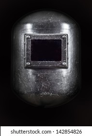 A welders Helmet front view, low key lighting.